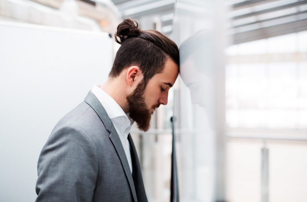 A sad and frustrated young businessman in suit standing in office, head against wall.