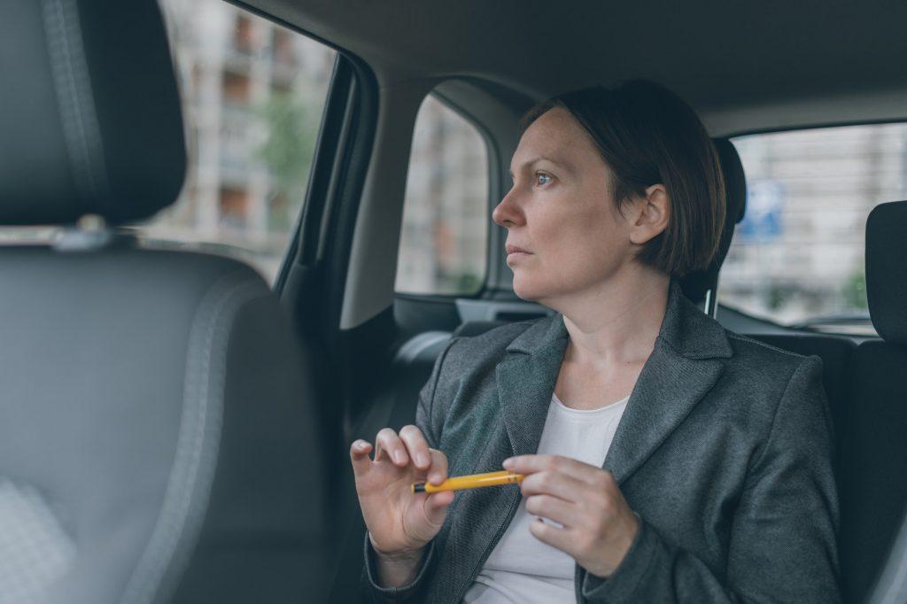Businesswoman waiting at car back seat
